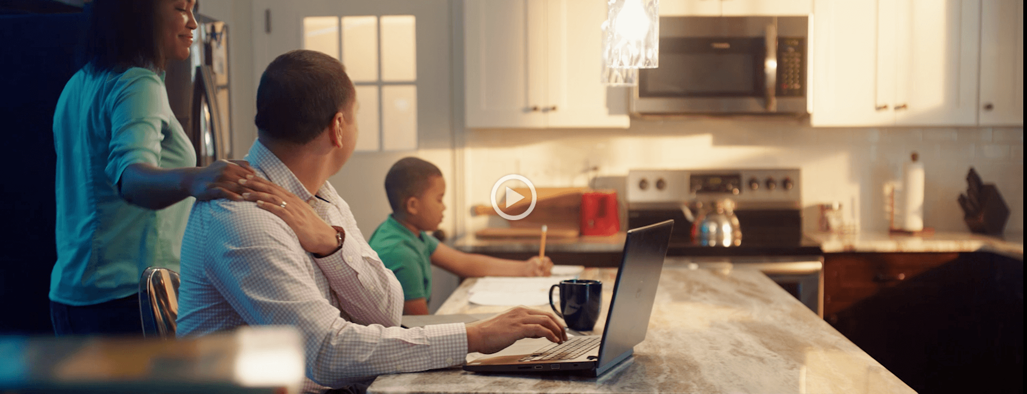 man on computer with family in kitchen